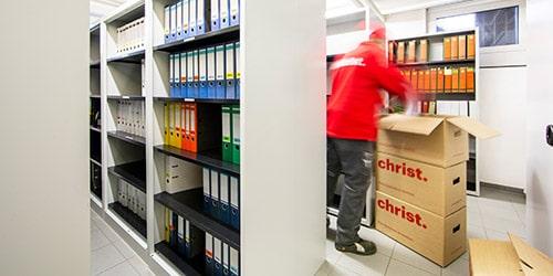 Mitarbeiter packt Ordner in Karton bei Archivumzug