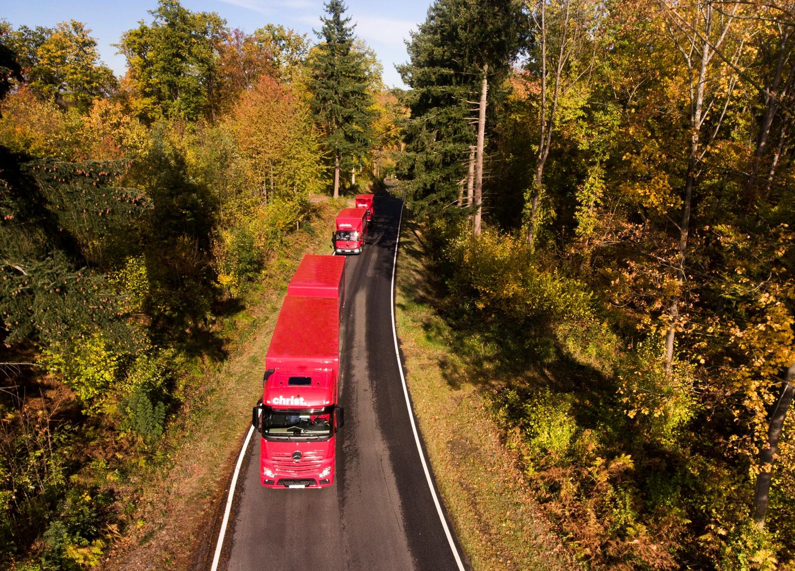 Christ Logistik LKWs fahren auf Landstraße - Sicht von oben