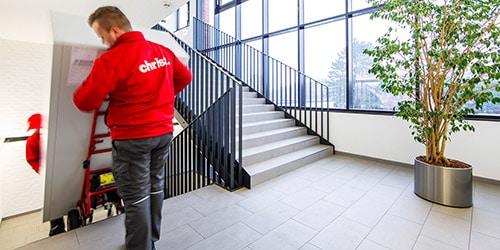 Christ-Logistik-Mitarbeiter transportieren großen Schrank die Treppe runter