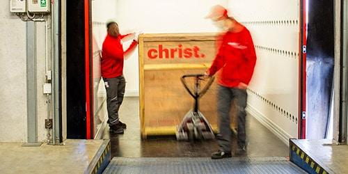 Mitarbeiter laden Holzkisten in LKW für Messelogistik