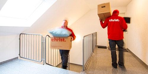 Christ Mitarbeiter tragen Umzugskartons bei Standortwechsel