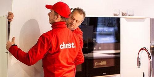 Zwei Christ-Mitarbeiter bauen Küchenmöbel bei Umzug auf