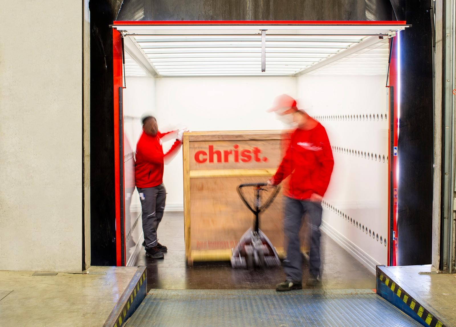 Zwei Christ Logistik Mitarbeiter holen große Holzkiste aus LKW